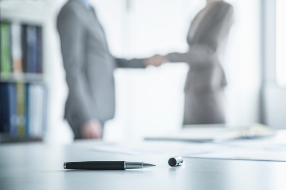 An image of a businessman and a businesswoman shaking hands in an office with books, a table with a pen, and documents.
