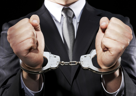 An image of a businessman in a black suit and gray tie with his hands in handcuffs.