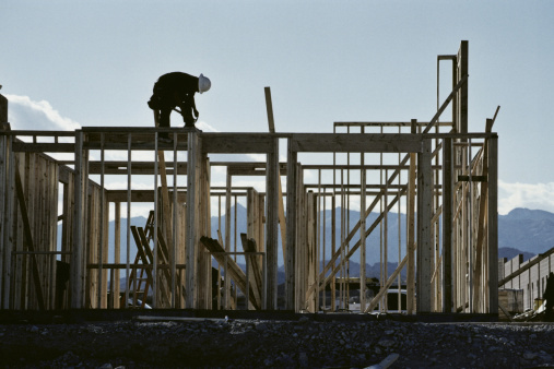 Construction worker with a white hard hat building the wooden frame of a house outside, with mountains, and the sky showing