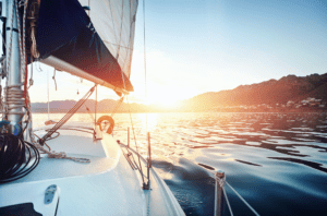 Looking aft on a sailboat into the sunset stock photo used by Woodruff Sawyer.