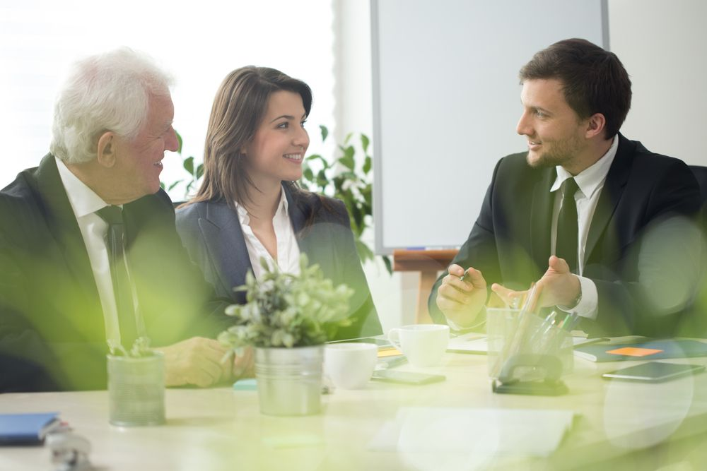 An image of two businessmen and a businesswoman in suits talking at a table with items on it.