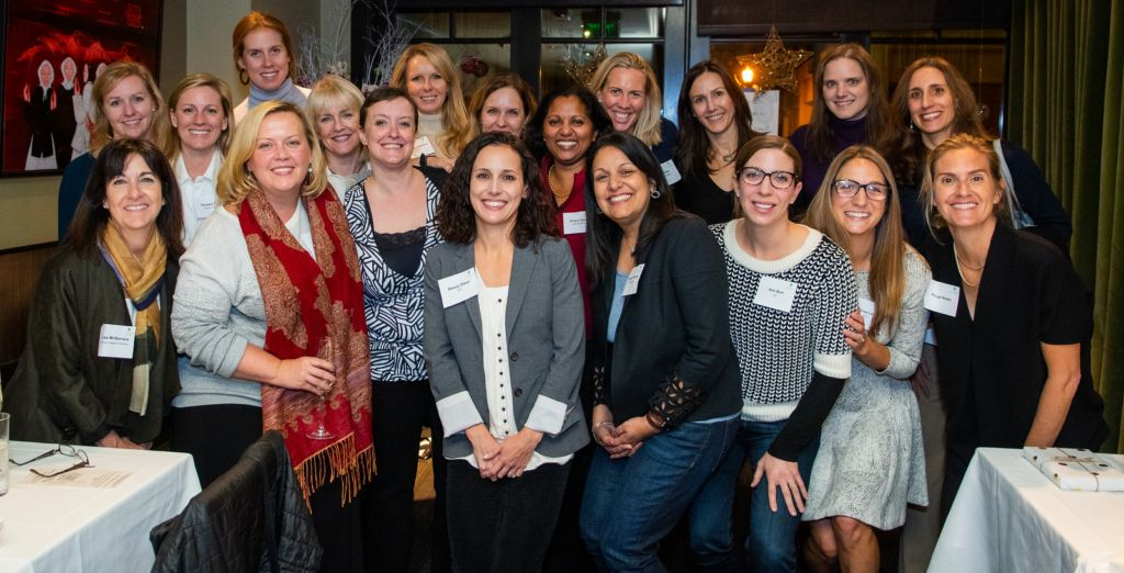 An image of women smiling in a conference room for the Executive Women Network Event 2018.