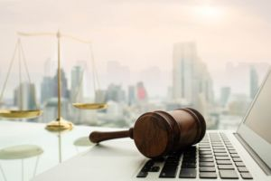 Gavel on laptop with city in background
