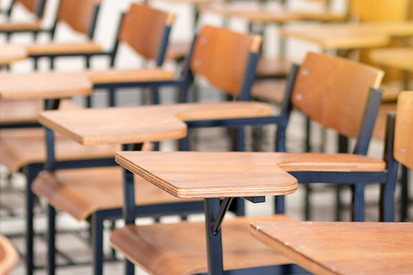 Old wooden desks in a classroom stock photo used by Woodruff Sawyer.