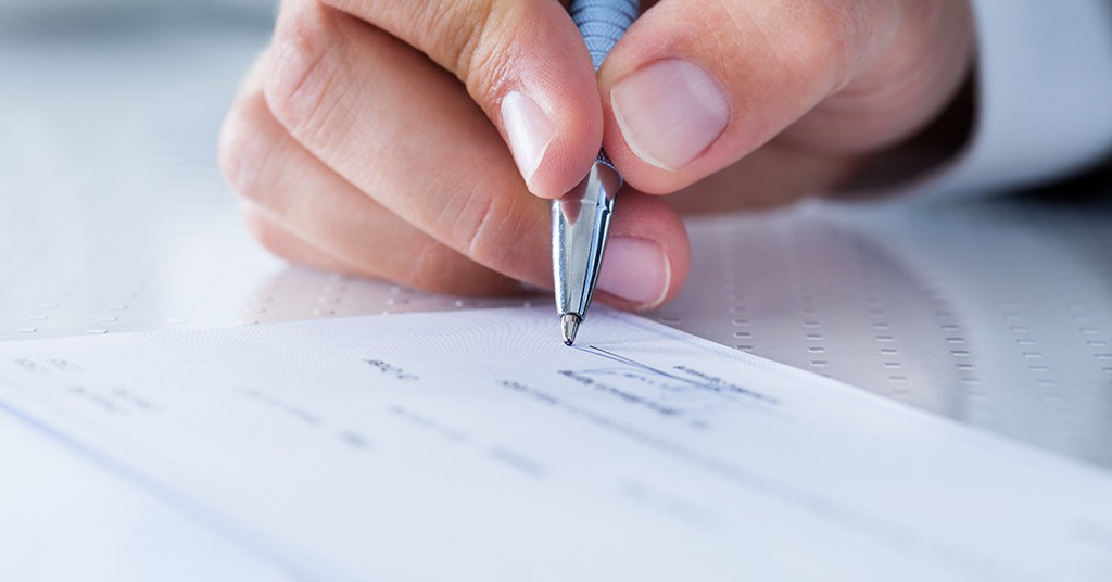 signing a check with a pen