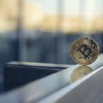 Bitcoin cryptocurrency on edge of office desk