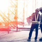 image of a construction site with two contractors reviewing plans