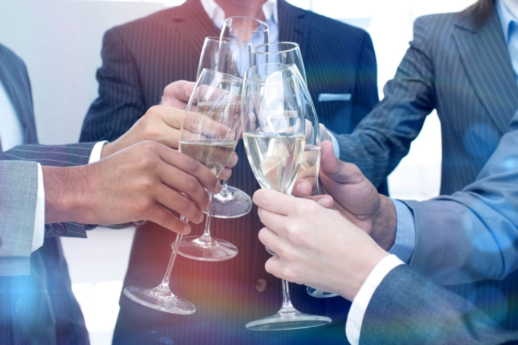 Image of six people in business suits holding champaign glasses
