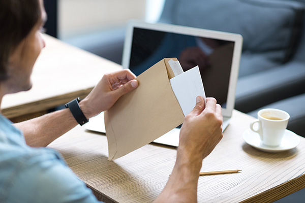 Image of a man opening a letter