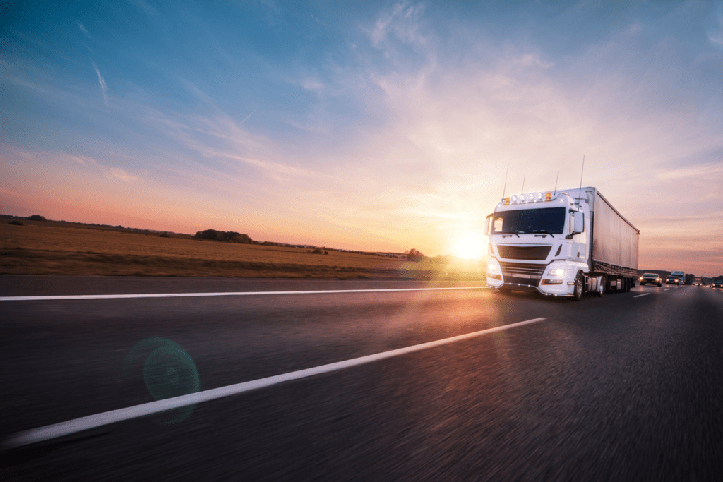 Large freight truck driving down highway during sunset