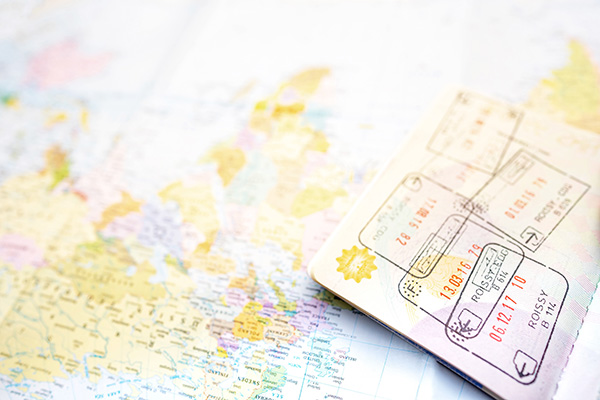 Image of an open passport with customs stamps lying on top of a world map