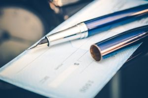 Blank check with a fountain pen lying on it stock photo used by Woodruff Sawyer.