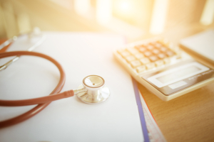 Financial papers on desk with calculator and stethoscope