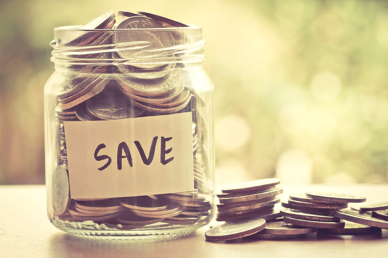 Glass jar filled with money coins for savings