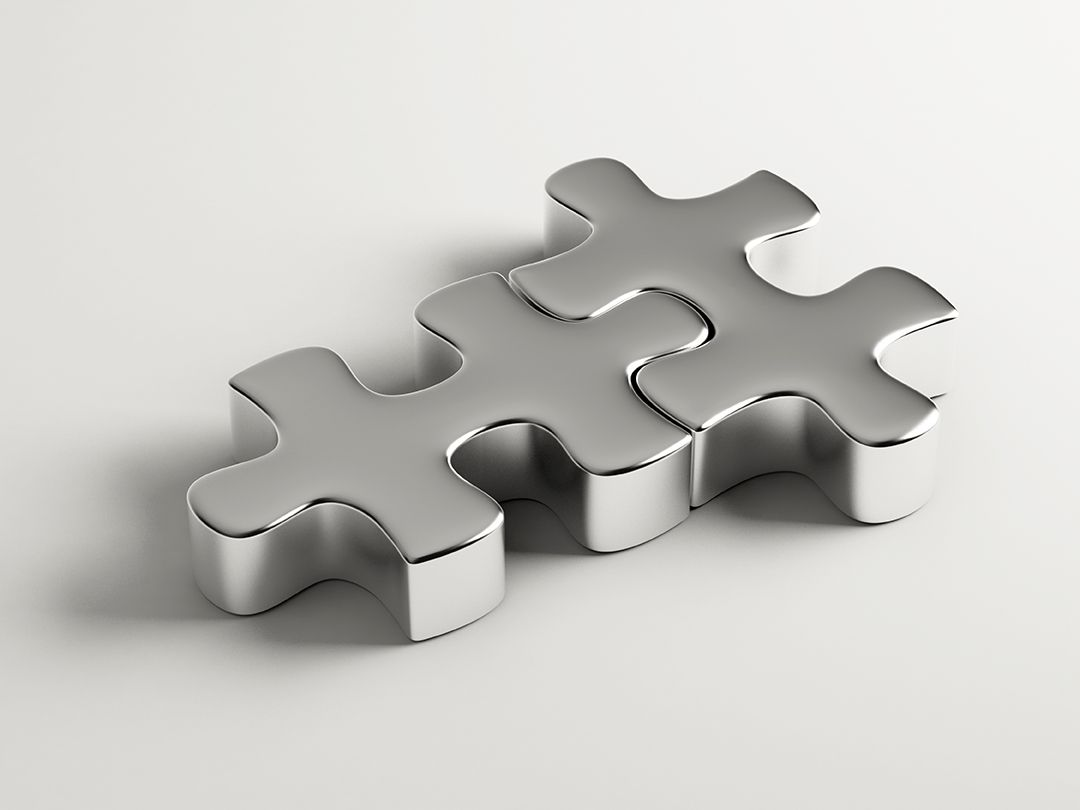 Two metal puzzle pieces fitting together