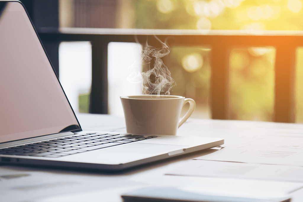 Laptop next to coffee cup on outdoor table with sun shining