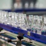 Bottles on conveyor belt at manufacturing plant