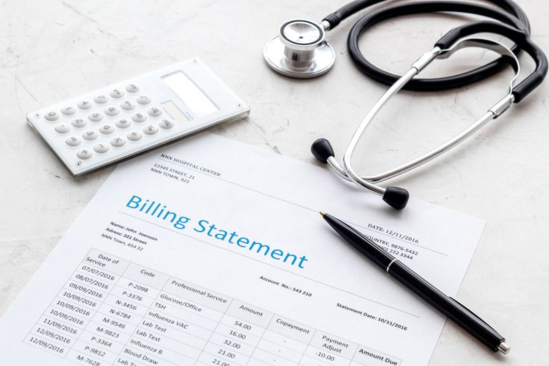 Medical billing statement with a pen, calculator and stethoscope