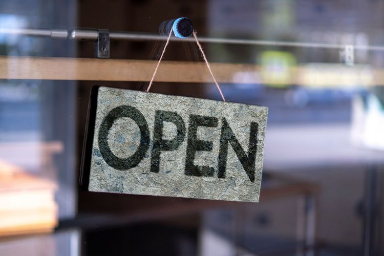 Open sign hanging on glass window of a business storefront