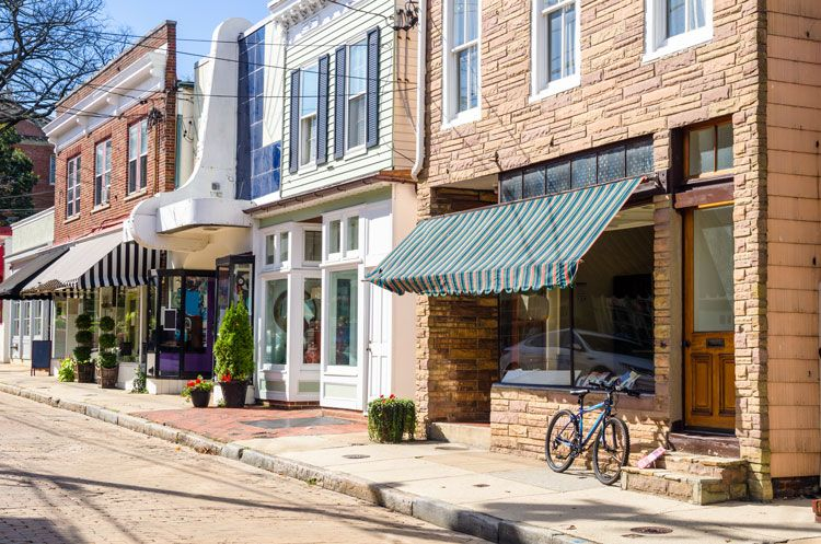 Bike leaning on storefront along cobblestone street