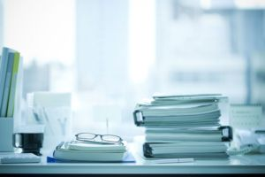 Stack of binders and administrative paperwork on desk