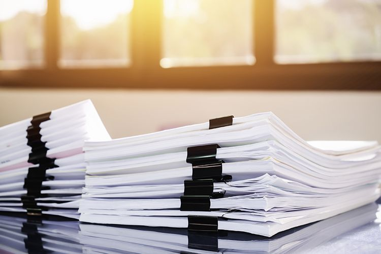 Stack of paperwork on table near window