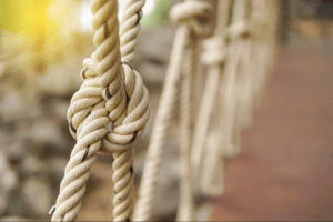 Rope knots on a bridge while the sun is shining outside.