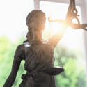 Statue of Justice in front of a brightly lit window