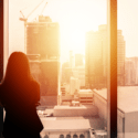 businesswoman looking out a conference room window