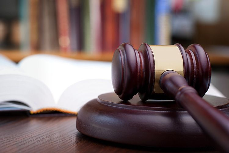 Gavel on table with legal books