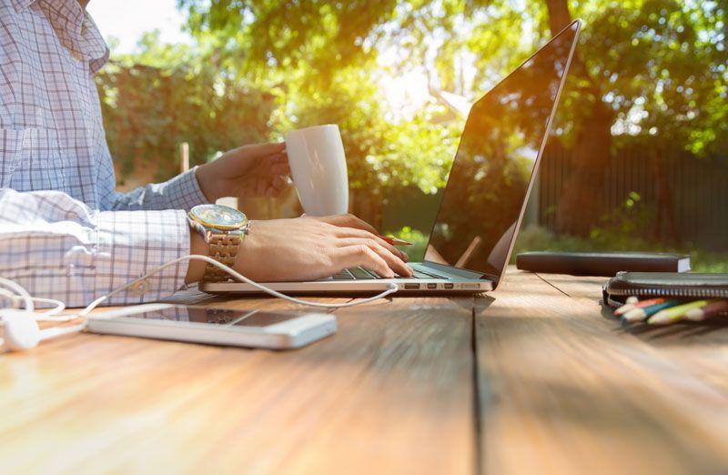 employee working outside coffee laptop